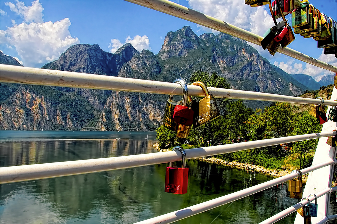 security locks on bridge with mountains in the background