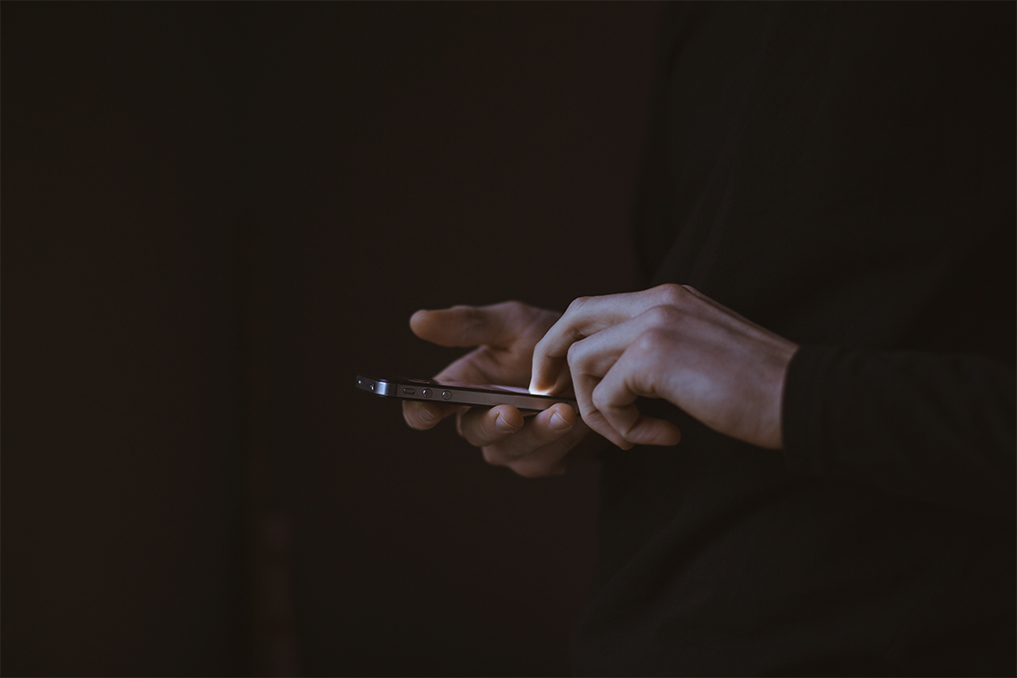 a pair of hands using an iPhone to view a WordPress website in the dark