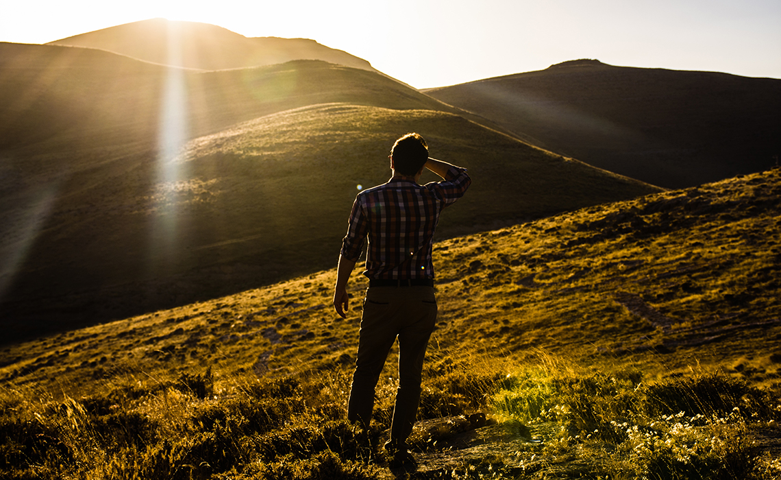 man searching in a hilly area