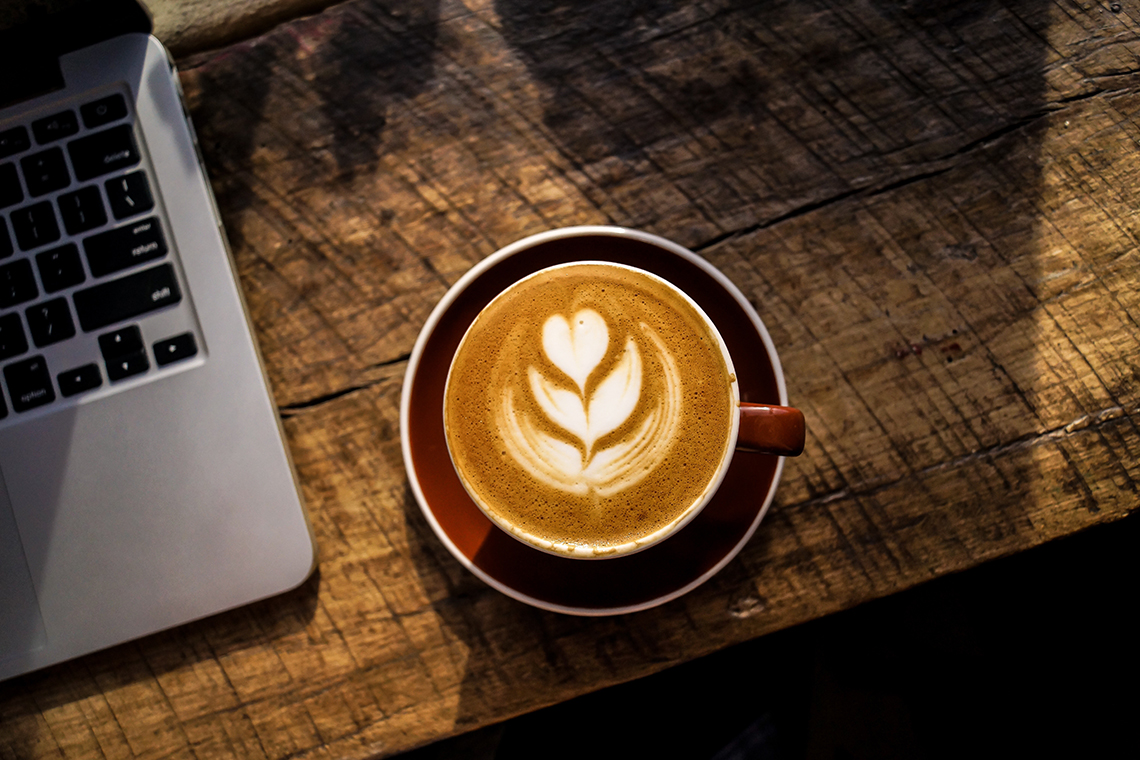 coffee next to macbook