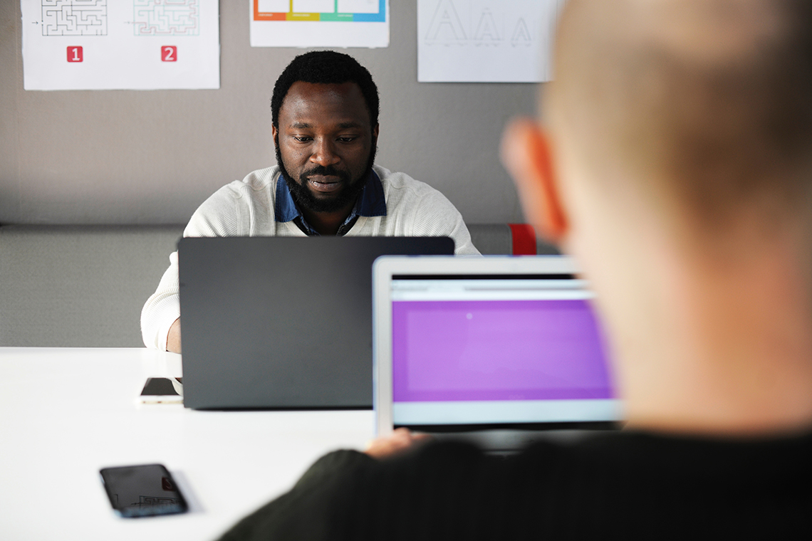 men looking at laptops
