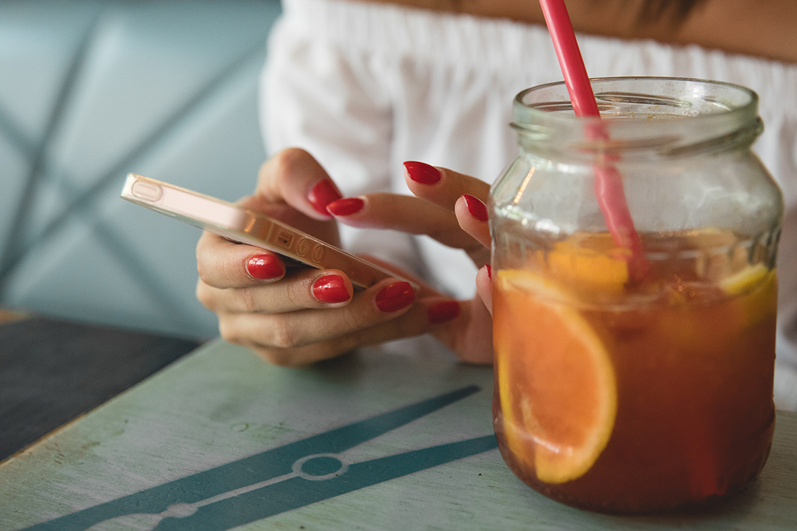 lady using social media on her phone with a refreshing drink