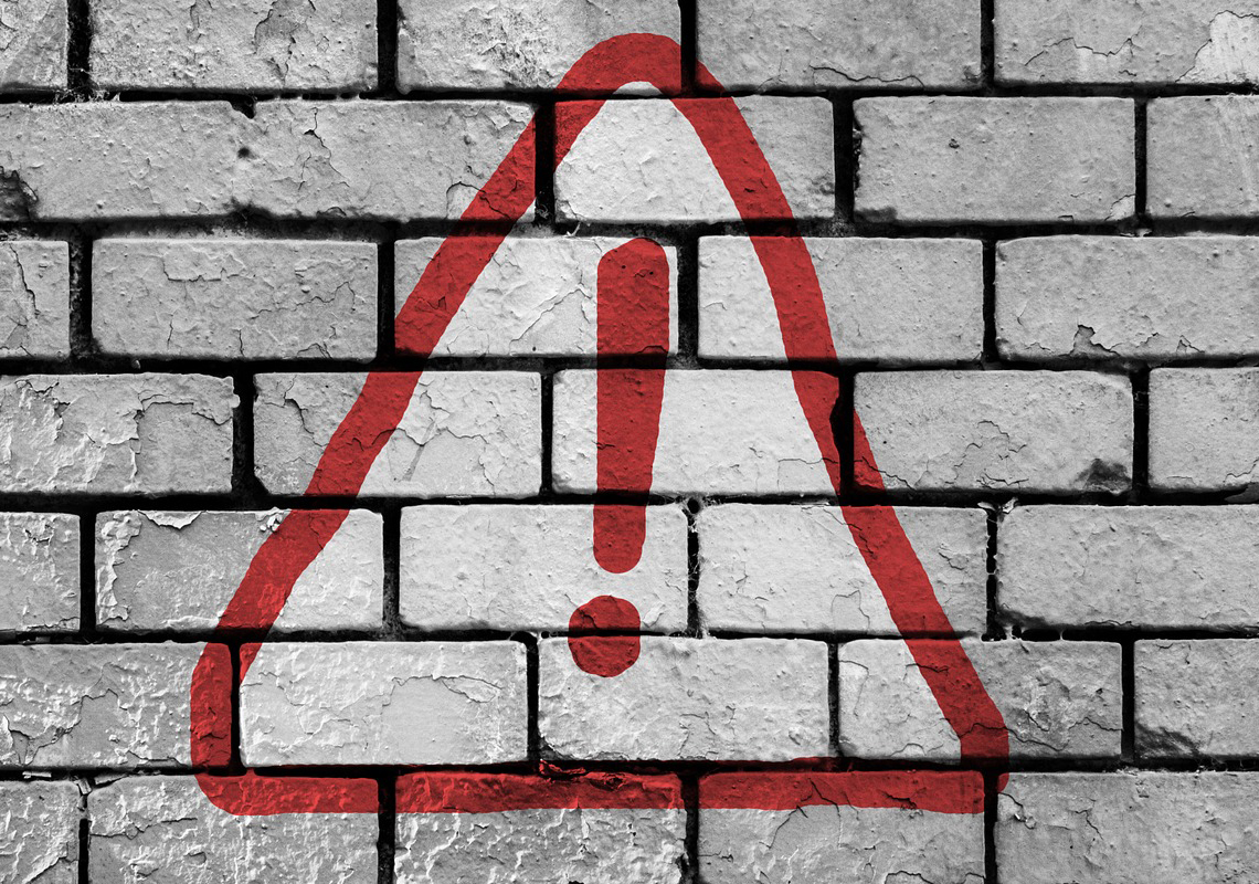 warning symbol on brick wall