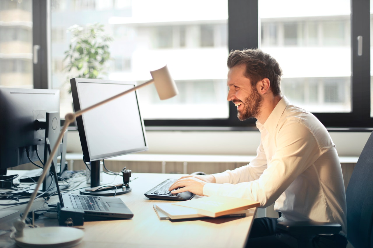 man laughing reading content shared on social media at his desk