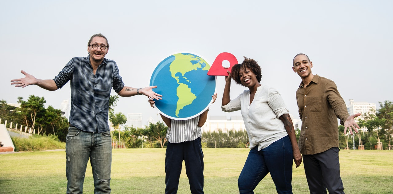 4 local people standing around a globe pointing to their area