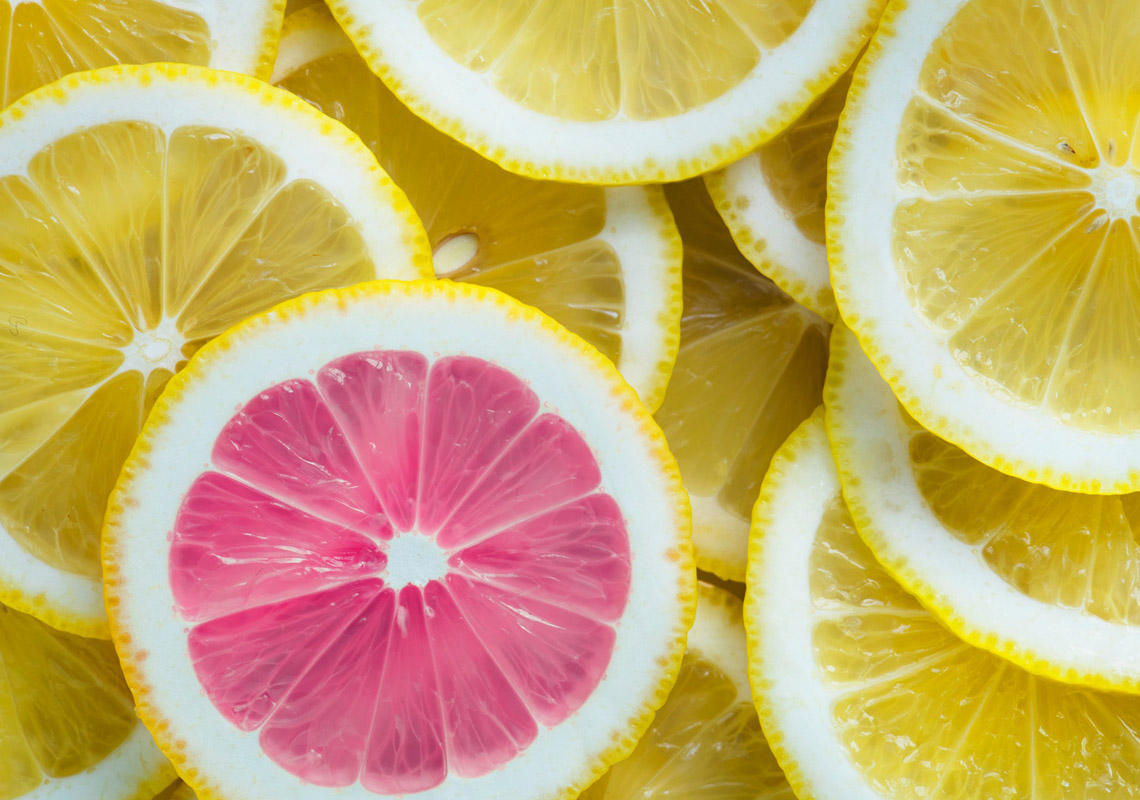 a unique pink slice of lemon among other slices of lemon