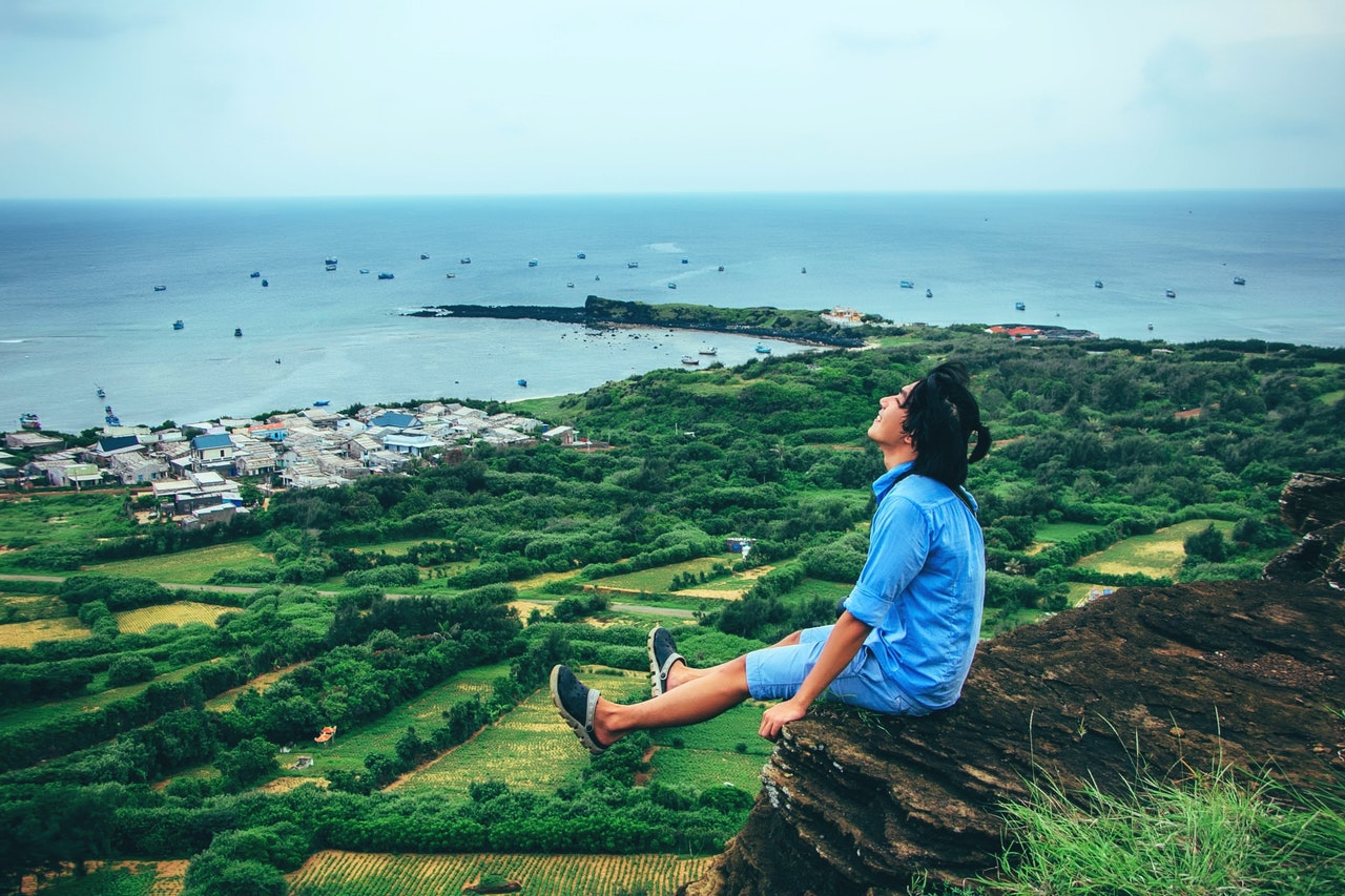 man sitting on cliff relaxing due to never running out of content ideas