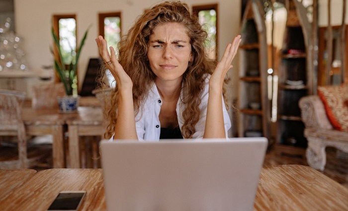 ginger haired lady confused at laptop